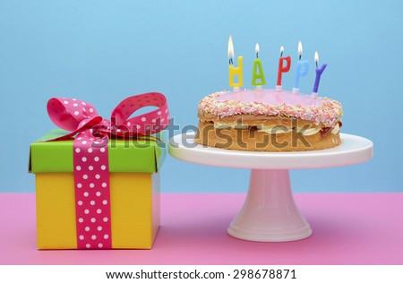 Bright color gift box with cake and candles on modern pink and blue background.  - stock photo