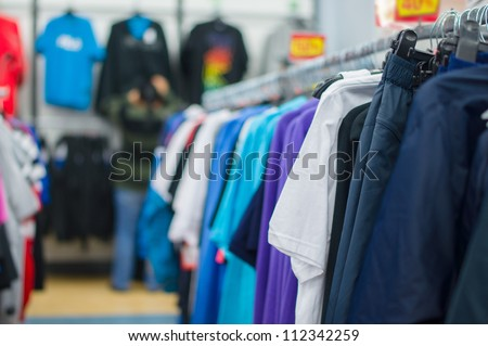 Bright color t-shirts and trousers on stands in supermarket - stock photo