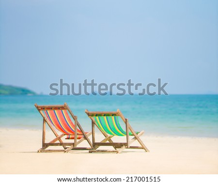 Bright color wooden beach chairs on island tropical beach