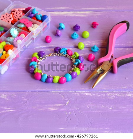 Bright colored bracelet made of plastic buttons. Handmade cute kids jewelry. Children's diy. Organizer with wooden and acrylic buttons, pliers.  - stock photo