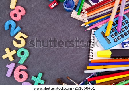 Bright colored figures and lots of school supplies on a black school board - stock photo