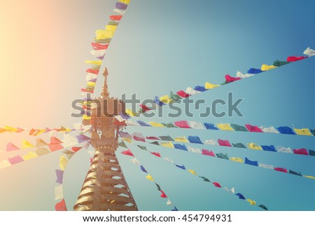 Bright colored flags attached to the spire of the building on the background of the blue sky