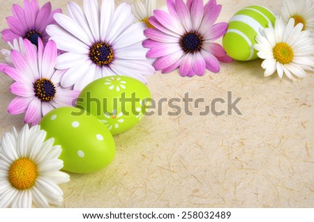 Bright-colored flowers and green Easter eggs as a border on rustic natural paper or parchment, with copysace - stock photo