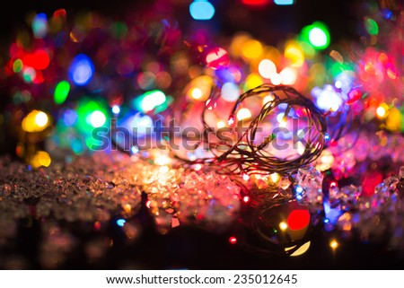bright colored garlands bulb shines in the dark background,  selective focus - stock photo