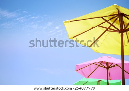 Bright colored umbrellas on the beach. - stock photo