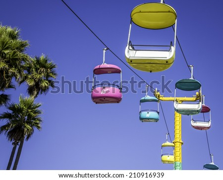 Bright colorful cable car ride against a clear blue sky - stock photo