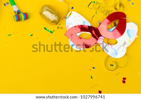 Bright colorful carnival or party scene of confetti and masks on yellow table. Flat lay, birthday or festive party card with copy space.