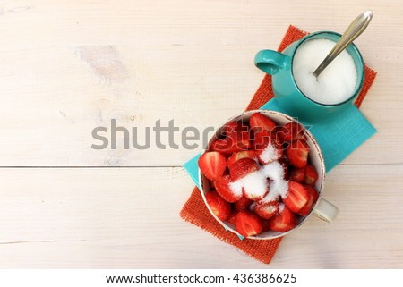 Bright, colorful composition with bowl full of ripe tasty strawberry, cup of sugar and couple of textile linen napkins on white wooden background. Contrast of red, orange and blue color. Copy space - stock photo