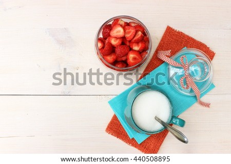 Bright, colorful composition with bowl full of ripe tasty strawberry, cup of sugar and couple of textile linen napkins on white wooden background. Contrast of red, orange and turquoise/blue color - stock photo