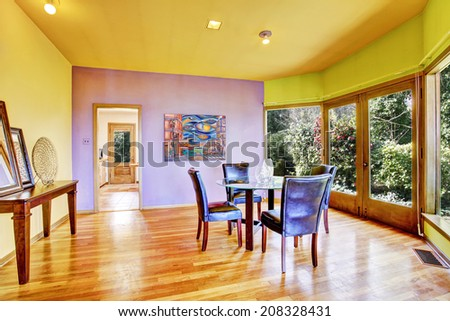 Bright colorful dining room with walkout deck. Furnished with round table and leather chair