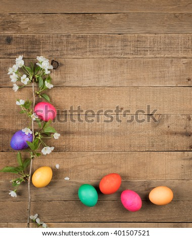 Bright, Colorful Easter Eggs on side and bottom of Rustic Wood Boards Background with blank room or space for copy, text, your words and with white spring tree flowers.   Vertical aerial top view
