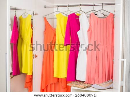 bright colorful female dresses hanging on coat hanger,  shoes and handbag in white wardrobe - stock photo