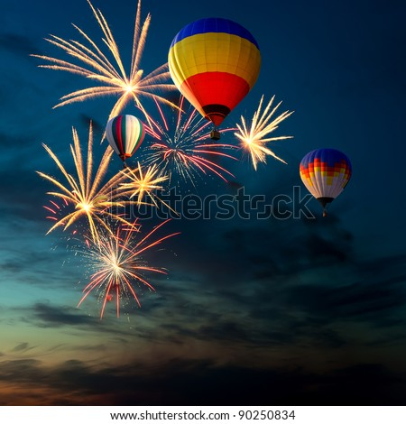 bright colorful fireworks and hot air-balloon of various colors in the night sky at sunset - stock photo