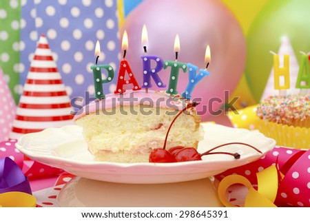 Bright colorful Happy Party Table with balloons, streamers, party favor gift bags with slice of cake and lit candles spelling party.