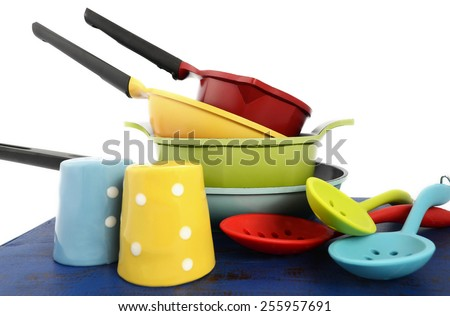 Bright colorful modern kitchen pot and pans in red, yellow, blue and green theme with spoons and salt and pepper shakers, on dark blue rustic wood table. - stock photo
