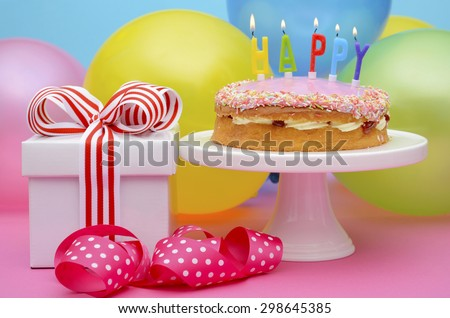 Bright colorful party table with balloons and gifts with bright color ribbons and bows, and Happy Birthday cake on cake stand.  - stock photo