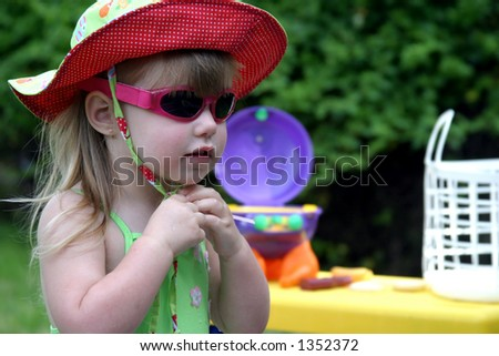 Bright, colorful picture of toddler girl in swimsuit, sunglasses and summer hat. - stock photo