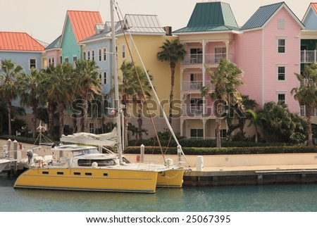 Bright colorful sea harbor in tropical island with sail boat - stock photo