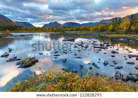 Bright colorful sunset with sky reflected in Polygonal freshwater lake surrounded by autumn taiga forest in Hibiny mountains above the Arctic Circle - stock photo