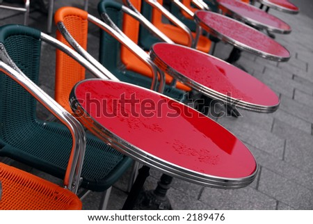Bright colorful tables in a sidewalk cafe on a rainy day - stock photo
