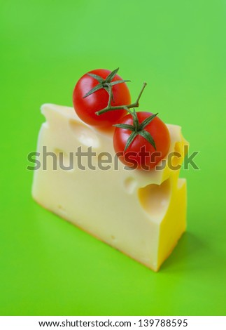 Bright colorful tasty and delicious still life made of two red ripe fresh cherry tomatoes with stems on top of a piece of cheese with big internal holes against bright green background. Copy space - stock photo