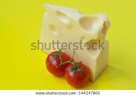 Bright colorful tasty and delicious still life made of two red ripe fresh cherry tomatoes with stems near a piece of cheese with big internal holes against yellow background. Copy space - stock photo