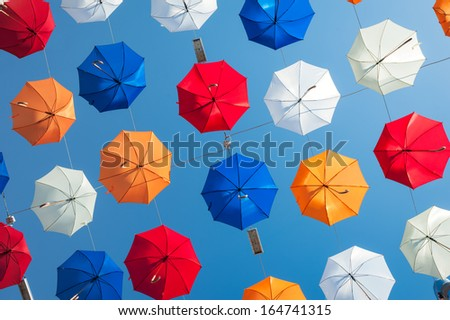 bright colorful umbrelas on blue sky background - stock photo