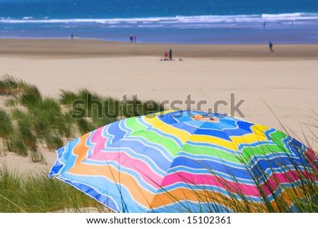 Bright, colorful umbrella on the beach - stock photo