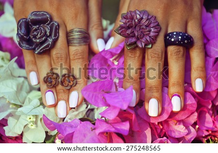 bright colorfull shot of african tanned hands with manicure among pink flowers wearing jewellery among flowers