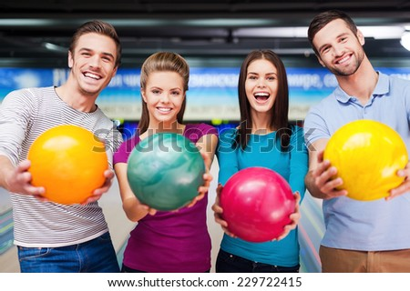 Bright colors of the best game. Cheerful friends looking at camera and outstretching their balls while standing against bowling alleys  - stock photo