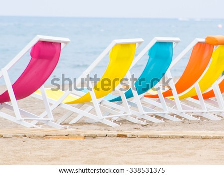 Bright colors sun chairs on the sand beach of Mediterranean sea - stock photo