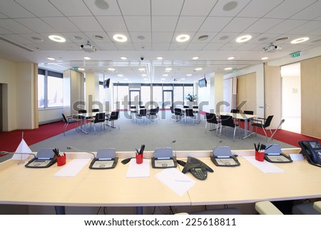 Bright conference room with four tables and modern equipment - stock photo