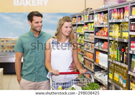 Bright couple buying products in aisle at supermarket - stock photo