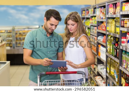 Bright couple using digital tablet at supermarket - stock photo