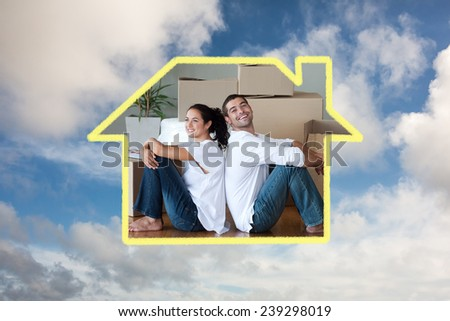 Bright couple with unpacking boxes moving to a new house against blue sky with white clouds - stock photo