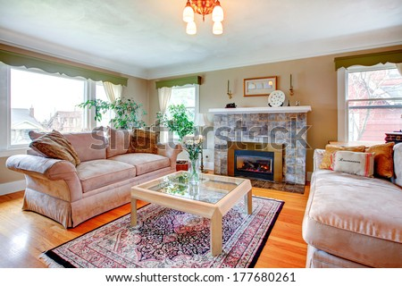 Bright cozy living room with hardwood floor and rug, fireplace, piano and comfortable sofas.  Table decorated with fresh white flowers - stock photo