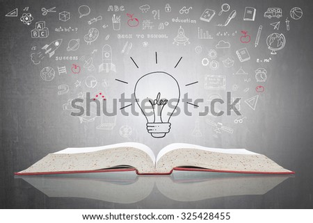 Bright creative idea light bulb over open textbook (shallow focus) with white freehand doodle sketch drawing of educational knowledge wisdom floating on black cement concrete chalkboard background  - stock photo