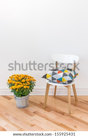 Bright cushion on a chair, and orange chrysanthemums decorating a room. - stock photo
