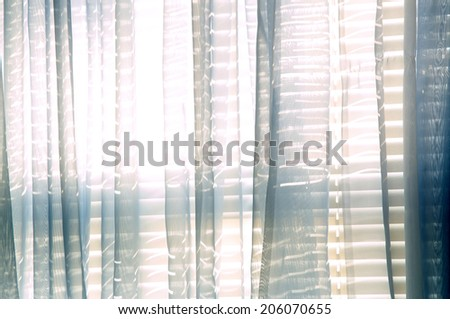 Bright daylight shines through a window draped with blue sheer curtains in this semi abstract high key image. - stock photo