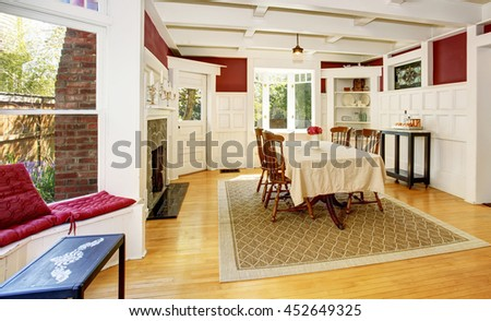 Bright dining room in red walls and white wooden trimmings. Also fireplace with stone decor and light brown hardwood floor.