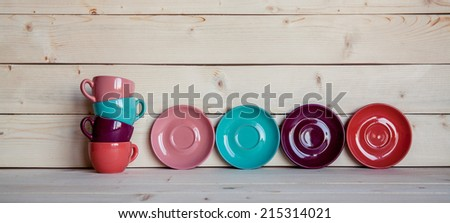 Bright dishes on table on a wooden background - stock photo