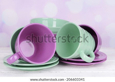 Bright dishes on table on bright background