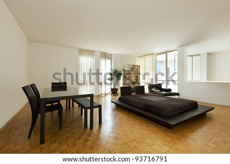 Bright duplex with hardwood floors, large room with double bed and table - stock photo