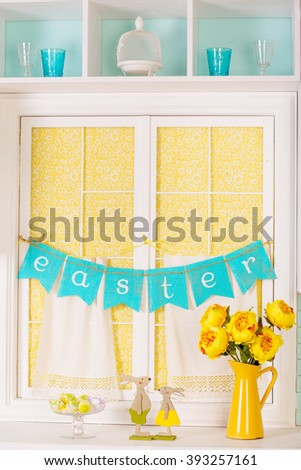 Bright Easter decor. Turquoise garland of flags on a white kitchen window. Nearby is a bouquet of yellow flowers, Easter bunnies and eggs - stock photo