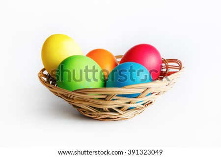 Bright Easter eggs in basket. Colorful easter eggs. - stock photo