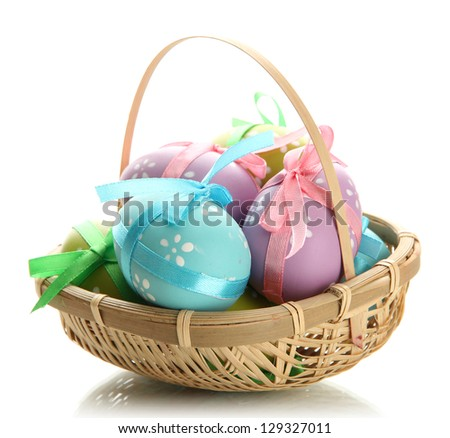 Bright easter eggs with bows in basket, isolated on white - stock photo