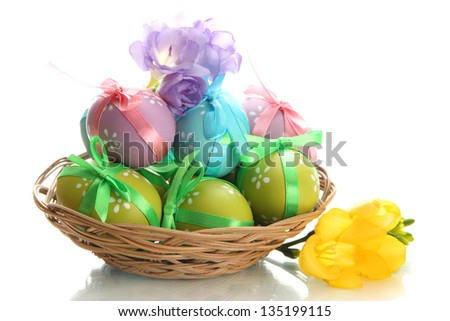 Bright easter eggs with bows in basket, isolated on white