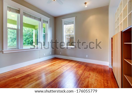 Bright empty room with hardwood floor and built-in wall shelves - stock photo