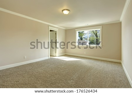 Bright empty room with one window, beige carpet floor and ivory walls