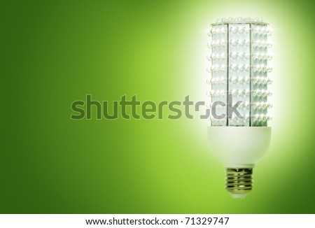 Bright, energy efficient light bulb consisting of 224 separate diodes, against green background. - stock photo